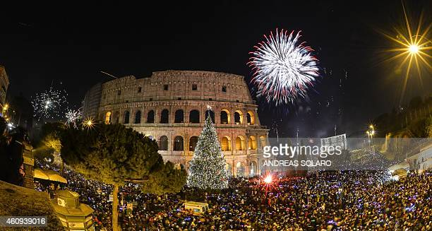 People cheer in front of Rome's ancient Colosseum as fireworks explode to celebrate the new year on January 1 2015 AFP PHOTO / ANDREAS SOLARO