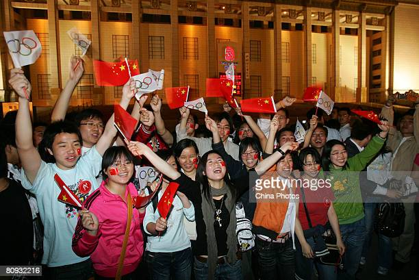 People cheer in front of the countdown board for the Beijing 2008 Olympic Games at the National Museum, on the day marking the 100-day-countdown to...