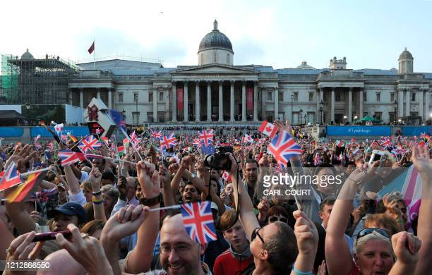 People cheer in Trafalgar Square as they attend a ceremony to unveil of the London 2012 gold silver and bronze medals to mark the oneyear countdown...
