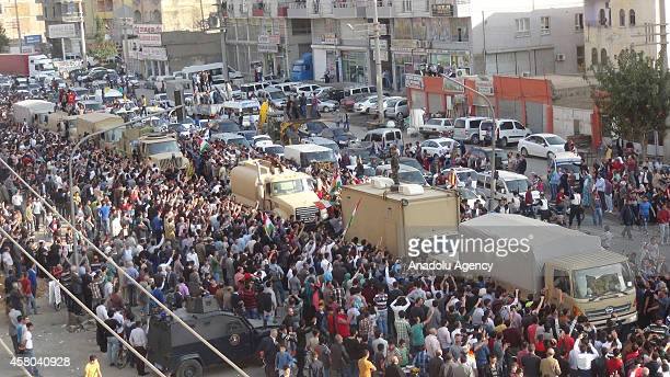 People cheer over passing of Iraqi Kurdish Peshmerga forces' military convoy carrying heavy weapons in Kiziltepe district of Mardin Turkey on October...