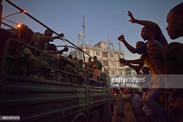 People cheer Senegalese ECOWAS soldiers as they arrive at the Statehouse in Banjul on January 22, 2017. - West African troops approached the Gambian...