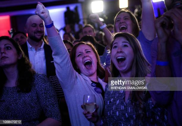 TOPSHOT People cheer to live results while attending a midterm election night party hosted by the Democratic Congressional Campaign Committee...