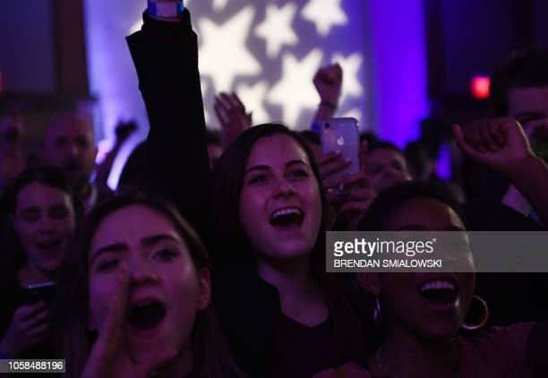 People cheer while watching election results during a midterm election night party hosted by the Democratic Congressional Campaign Committee November...