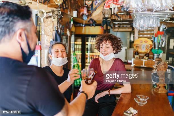 menschen, die mit bier in der bar mit maßnahmen zur krankheitsprävention jubeln, werden getroffen - corona beer stock-fotos und bilder