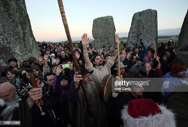 People cheers as the sun rises as druids pagans and revellers celebrate the winter solstice at Stonehenge on December 21 2012 in Wiltshire England...