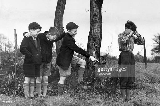 1940's Three schoolboys in long socks short trousers blazers and caps 'poke fun' at another boy's dress sense