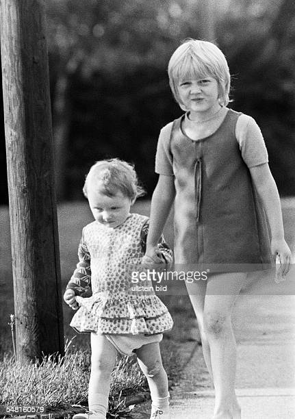 People, children, girl and younger sister going hand in hand for a walk, aged 6 to 9 years, aged 3 to 4 years -
