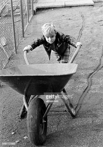 people children little boy moves a heavy wheelbarrow exertion aged 3 to 5 years