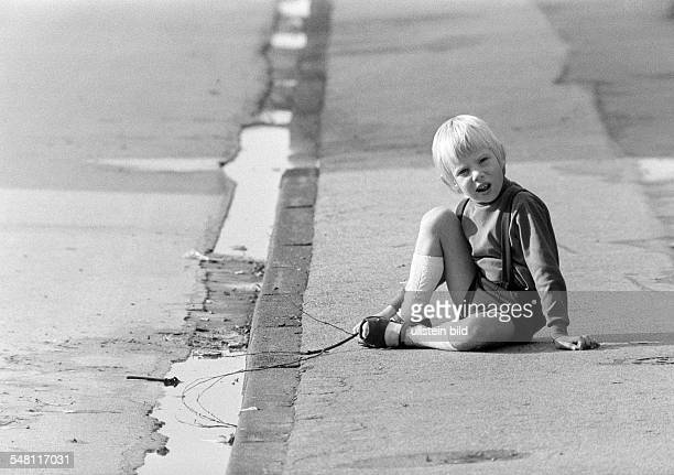 people children little boy sits on a pavement and plays with a stick in a puddle aged 3 to 5 years