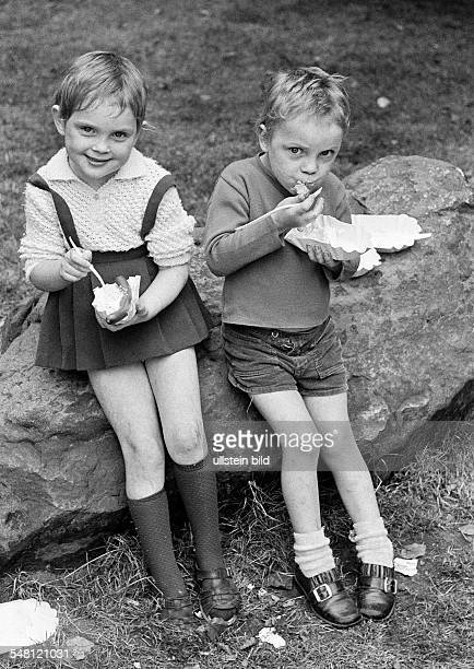 people children little girl and little boy sit side by side on a rock and eat fastfood sausage and potato salad aged 4 to 7 years