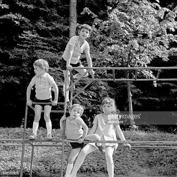 people children little girl and three little boys on a monkey bars childrens playground aged 4 to 8 years