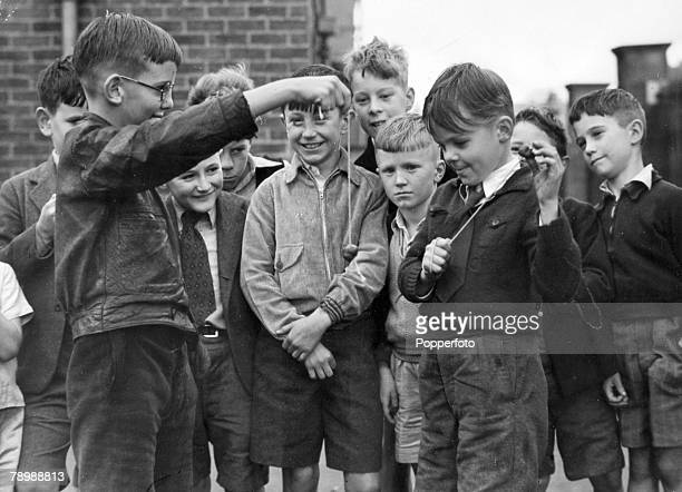 September 1952 Great Britain Boys playing 'conkers' in the street with other gathered around watching