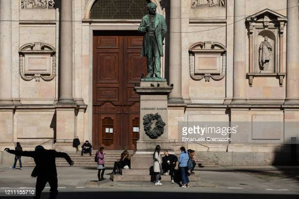 People chill under the statue of Italian writer Alessandro Manzoni in central Piazza San Fedele square on March 08 2020 in Milan Italy Prime Minister...