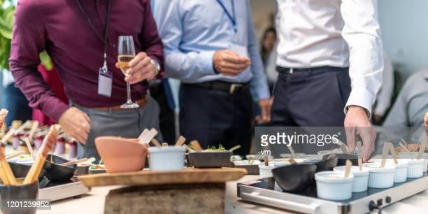 les gens choisissant la nourriture à un buffet d'entreprise - lunch photos et images de collection