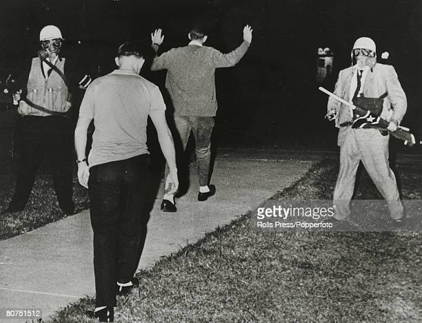 September 1962 Oxford Mississippi White student protesters are marched away by USMarshalls wearing gas masks after protests against black student...