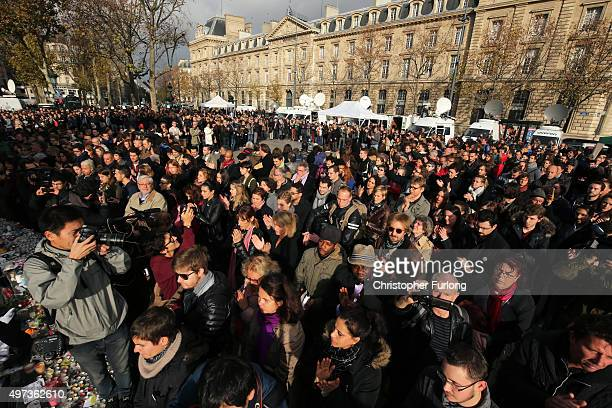 People clap at the end of a minutesilence at the Place de la Republique in memory of the victims of the Paris terror attacks last Friday on November...