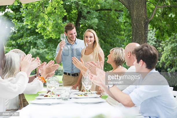 People clapping hands for young couple on a garden party