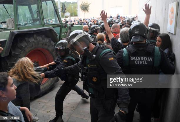 People clash with Spanish Guardia Civil guards outside a polling station in Sant Julia de Ramis where Catalan president is supposed to vote on...