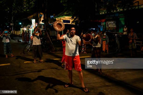 People clatter cymbals and pans to make noise after calls for protest went out on social media in Yangon on February 3 as Myanmar's ousted leader...