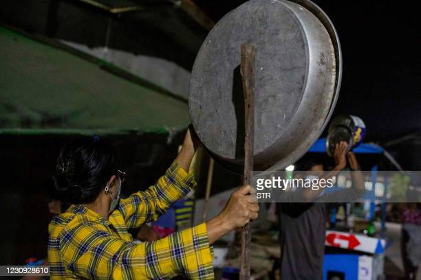 People clatter pans and tins to make noise to protest the military coup in response to a social media campaign in Yangon on February 2 as the party...