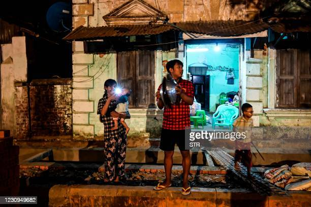 People clatter pans to make noise after calls for protest went out on social media in Yangon on February 3 as Myanmar's ousted leader Aung San Suu...