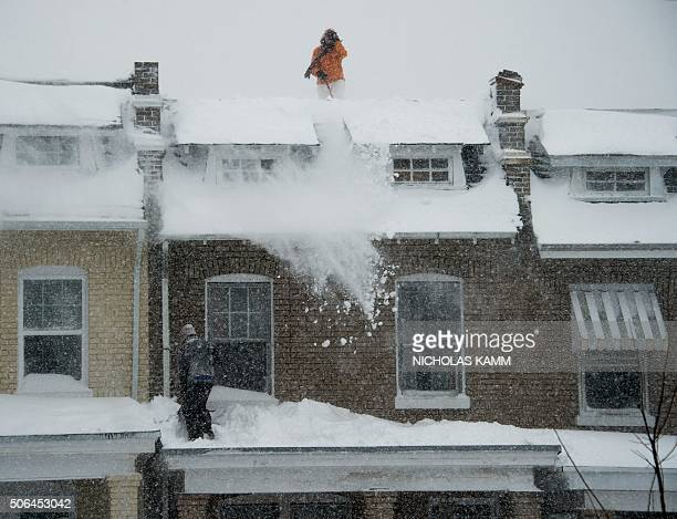 People cleaar snow from the roof of their house and porch during a snowstorm in Washington DC on January 23 2016 A deadly blizzard with bonechilling...