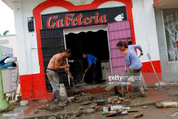 People clean a business damaged when the Arecibo River overflowed in Arecibo Puerto Rico September 30 2017 US military and emergency relief teams...