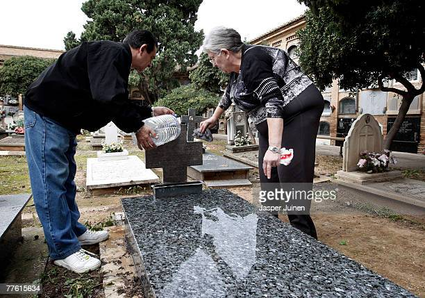 People clean a grave at the general cemetery on November 1 2007 in Valencia Spain Many Spaniards visit cemeteries on All Saints Day to pay respect to...