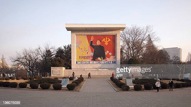 People clean a monument featuring North Korea's founding father Kim IlSung in central Pyongyang on December 23 2011 Millions of griefstricken people...