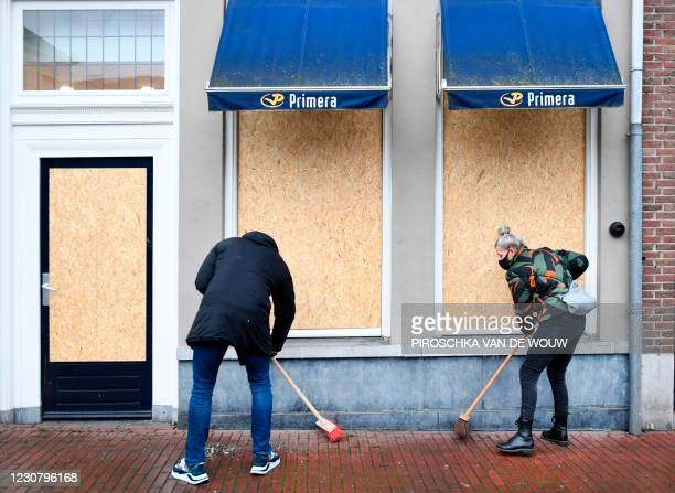 People clean a street in Den Bosch on January 26 a day after police clashed with groups of demonstrators against the introduction of a coronavirus...