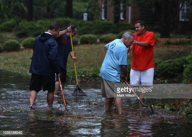 People clean debris away from the storm drains after Hurricane Florence hit the area on September 14 2018 in Wilmington North Carolina Hurricane...