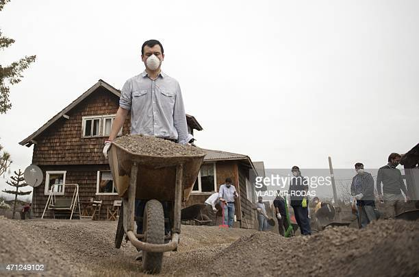 People clean the ash from the Calbuco volcano around their home at La Ensenada, southern Chile, on April 26, 2015. A sleeping giant for more than 50...