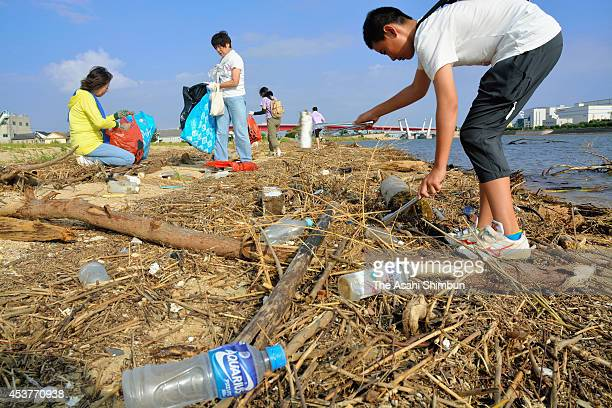 People clean the Omaehama beach on August 17, 2014 in Nishinomiya, Hyogo, Japan. Rubbish and logs are scattered as they washed ashore after Typhoon...