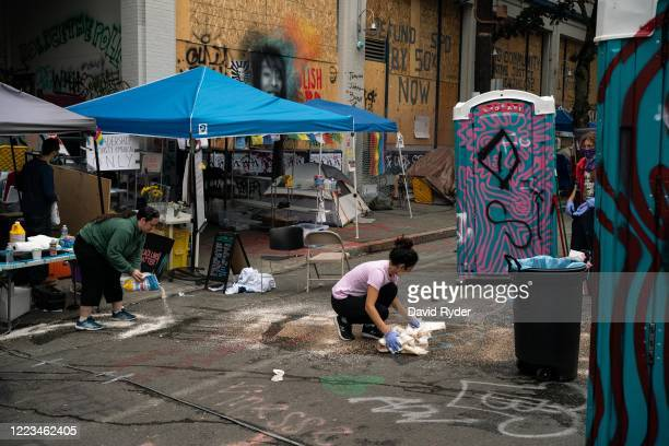 People clean the site of an early morning shooting that left one person dead and one in critical condition in the area known as the Capitol Hill...