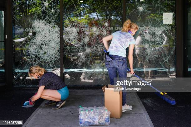 People clean up damage to CNN Center following an overnight demonstration over the Minneapolis death of George Floyd while in police custody on May...