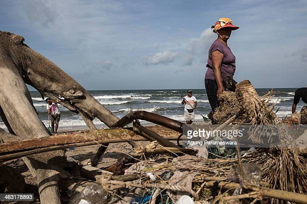 People clean up piles of the debris brought in by strong waves at Kuta Beach on January 17 2014 in Kuta Indonesia The sight of trash washed up on...