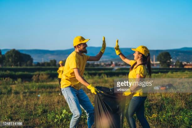 mensen die huisvuil in aard schoonmaken - activist stockfoto's en -beelden