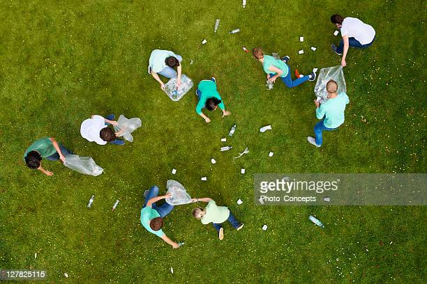 people cleaning up litter on grass - group of objects stock photos and pictures