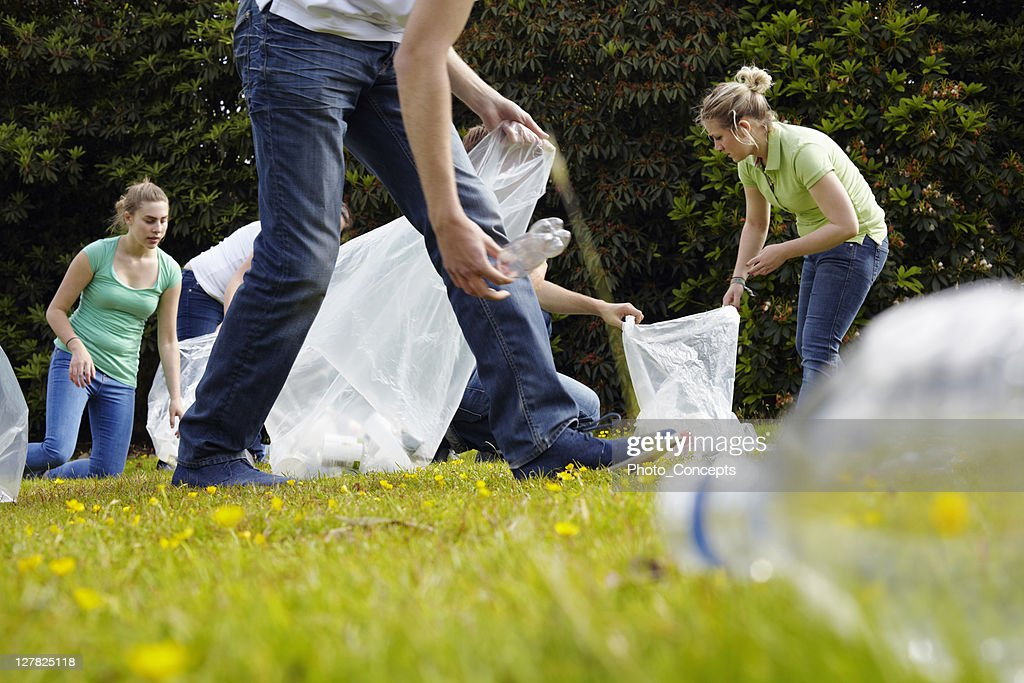 People cleaning up litter on grass : Stock Photo