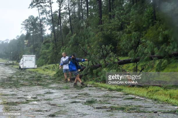 People clear a fallen trees during Hurricane Sally landfall on the outskirts of Mobile Alabama on September 16 2020 Hurricane Sally barrelled into...