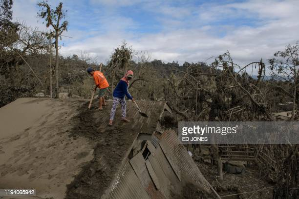 TOPSHOT People clear ash from their roof in the village of BusoBuso left from an eruption of the Taal volcano near Laurel on January 17 2020