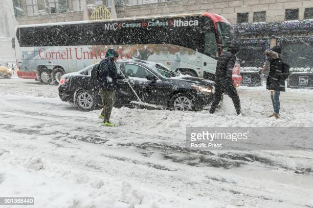 People clear car stuck in snow in Manhattan under heavy snow storm cold and wind A giant winter bomb cyclone hit the US East Coast on Thursday with...