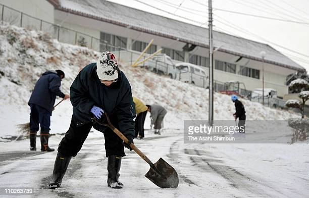 People clear snow and ice from the road on March 17 2011 in Minamisanriku Miyagi Japan Thousands have been killed as a result of the 90 earthquake...