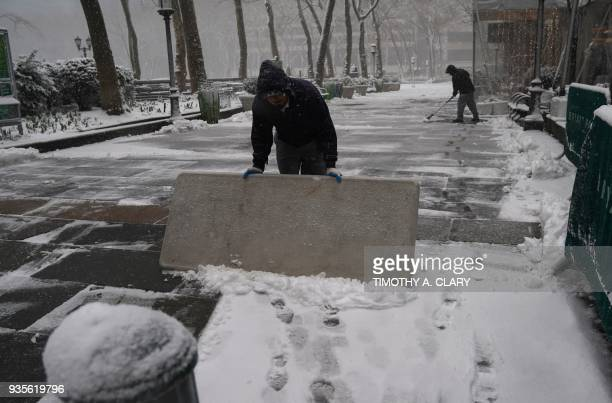 People clear snow at Bryant Park in NewYork on March 21 as the fourth nor'easter in a month hits the tristate area on the first full day of spring...