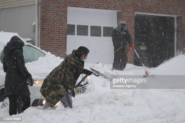 People clear snow in front of their house after heavy snowfall in Cliffside Park region of New Jersey, United States on February 01, 2021.