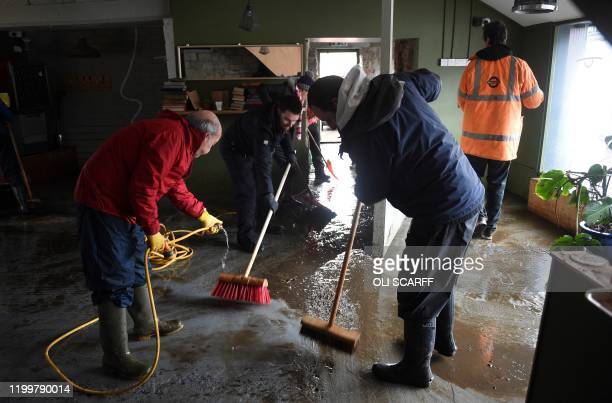 People clear up at a business in Mytholmroyd northern England on February 10 2020 after flooding brought by Storm Ciara Storm Ciara grounded hundreds...