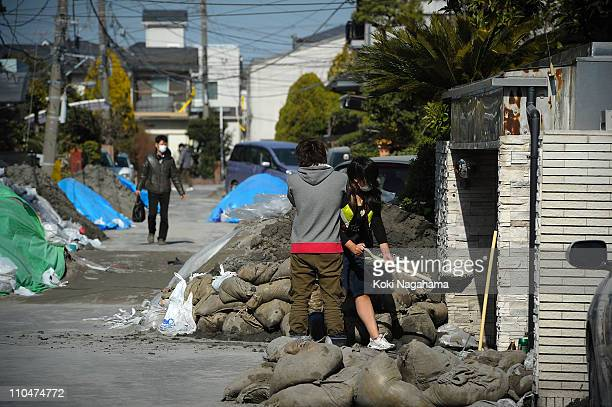 People clear up the mud due to the liquefaction triggered by the 90 magnitude earthquake on March 19 2011 in Urayasu Chiba Japan The reclaimed area...