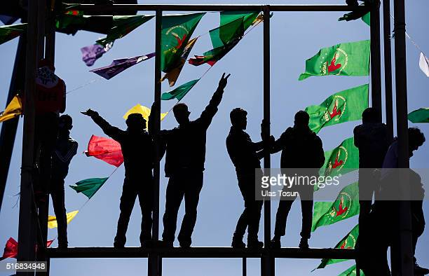 People climb a platform adorned with flags during Newroz celebrations on March 21 2015 in Diyarbakir Turkey Thousands of Kurds gather for the Newroz...