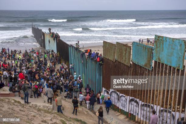 People climb a section of border fence to look into the US as members of a caravan of Central American asylum seekers arrive to a rally on April 29...
