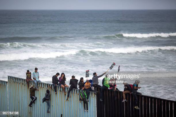 People climb a section of border fence to look toward supporters in the US as members of a caravan of Central American asylum seekers arrive to a...